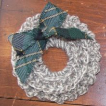 A hand crocheted wreath with a Maine Acadia Tartan bow.
